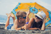 Mom and son are sunbathing on a beach — Stock Photo