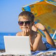 Happy smiling kid with laptop on a beach — Photo