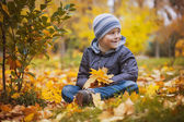 Happy kid on a background of autumn leafs — Stock Photo