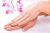 Manucure tendresse avec orchidée rose sur le blanc — Photo