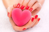 Red manicure with gift box on the white towel — Stock Photo