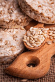 Crispbread, cereal crackers and wooden spoon with grain — Stock Photo