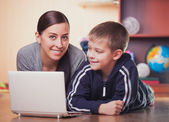 Mom and son are lying on wood floor with laptop — Stock Photo