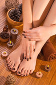 Brown manicure and pedicure on the bamboo — Stock Photo