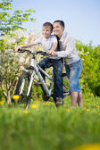 Boy on bike with mother — Stock Photo