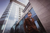 Fashion man in front of a glass building wearing coat — Foto Stock
