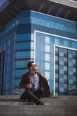 Handsome man is sitting on a skyscraper background — Stock Photo