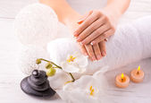 Beautiful hands with manicure and wnite orchid flower — Stock Photo