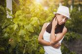 Young beautiful girl posing in fall vineyard — Stock Photo