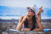Girl is lying on the beach with hat and swimsuit — Foto Stock