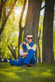 Man is sitting on the green grass in the park — Stock Photo