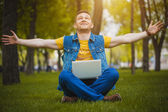 Young man in the park lying on grass with laptop — Stock Photo