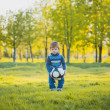 Funny boy is kicking ball in the field — Stock Photo