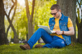 Young man in the park with laptop — Stock Photo