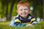 Little boy lying on the grass in the park — Stockfoto