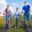 Happy family are riding bicycle in the field — Stock Photo
