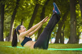 Pretty woman doing exercises in the park — Stockfoto