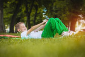 Happy kid is doing exercises in the park — Stockfoto