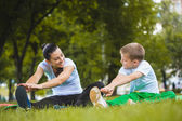 Son and mother are doing exercises in the park — Stock Photo