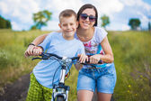 Mother and son riding bicycle in the field — Stockfoto