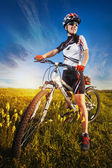 Woman riding bicycle in the field — Stock Photo