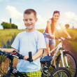 Happy family. mother and son riding bicycle in the field — Stock Photo #51797825