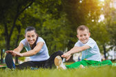 Zoon en moeder doen oefeningen in het park — Stockfoto