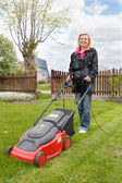 Woman with lawn mower — Stock Photo