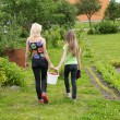 Mother and daughter walk home from the garden — Stock Photo