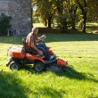 Stock Photo: Man driving a red lawn mower (tractor)