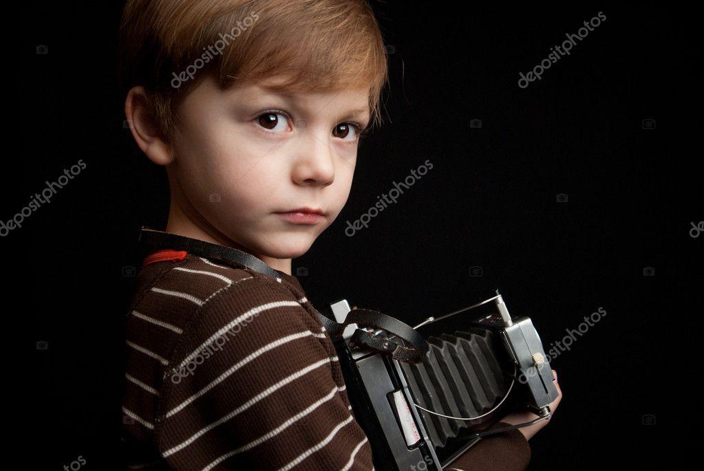 年轻的孩子拿着即时照相机在白色背景上