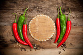 Red hot chili peppers on old wooden table — Stock Photo