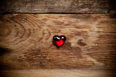 Corazón rojo sobre mesa de madera antigua — Foto de Stock
