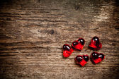 Red glassware hearts on old wooden table — Stockfoto