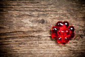 Red glassware hearts on old wooden table — ストック写真