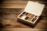 Assortment of spices in wooden box on old wooden table — Stockfoto