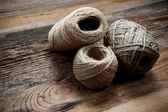 Three rope coils on old wooden background — Stock Photo