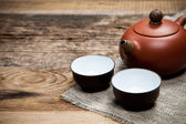 Tea cups with teapot on table — Stockfoto