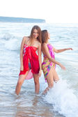 Two young women in a pareo on the sea — Stockfoto