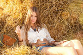 Beauty woman relaxing in the straw in field — Stockfoto