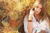 Красота женщины, расслабляясь в соломы в поле — Стоковое фото