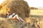 Beauty woman relaxing in the straw in field — Photo