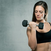 Beautiful sporty muscular woman with dumbbell — Stock Photo