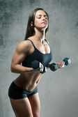 Beautiful sporty muscular woman with two dumbbells — Stock fotografie