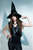 Beautiful witch stands and shows hat — Stockfoto