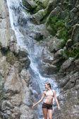 Waterfall with woman in bikini — Stock Photo