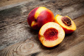 Fresh nectarines on wooden table — Stock Photo