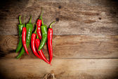 Red hot chili peppers on old wooden table — Stockfoto