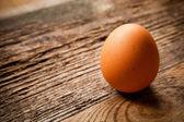 Jedno vejce na dřevěný stůl. — Stock fotografie