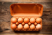 Eggs in the package on wooden table — Stock Photo